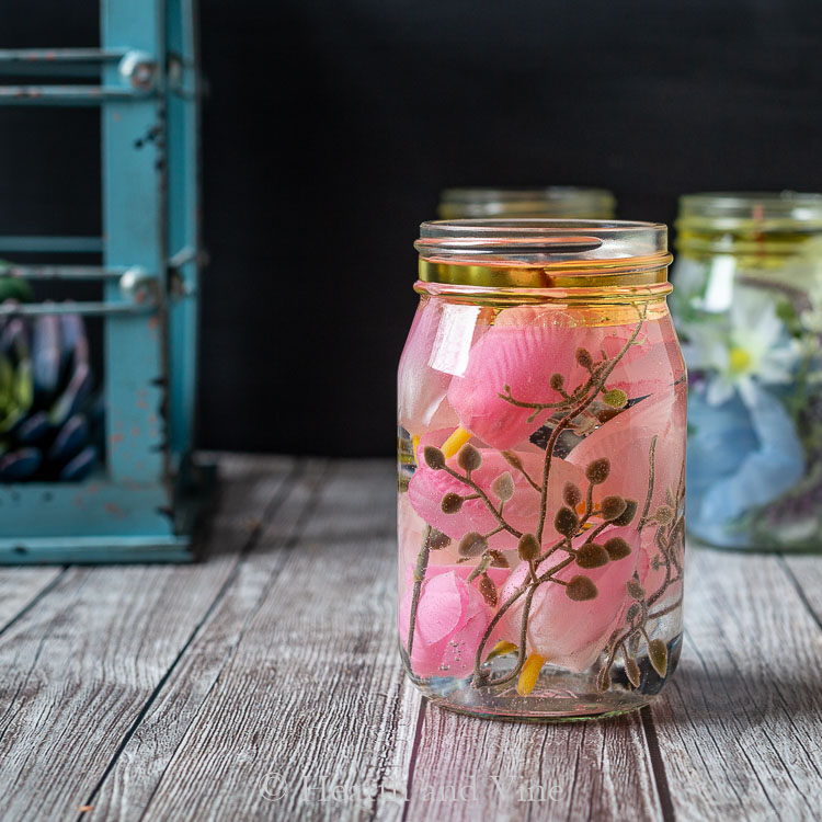 Mason jar oil candle with pink tulips and green leaves