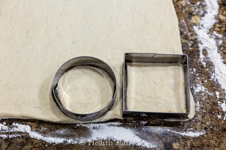 Round and square biscuit cutters on pizza dough