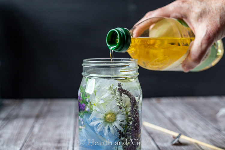 Pouring olive oil on top of water in filled mason jar