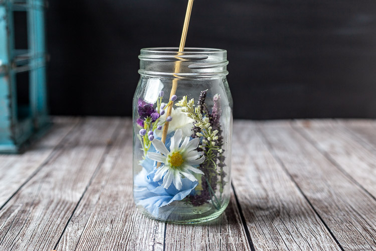Wooden skewer to move and pack flowers into mason jar.