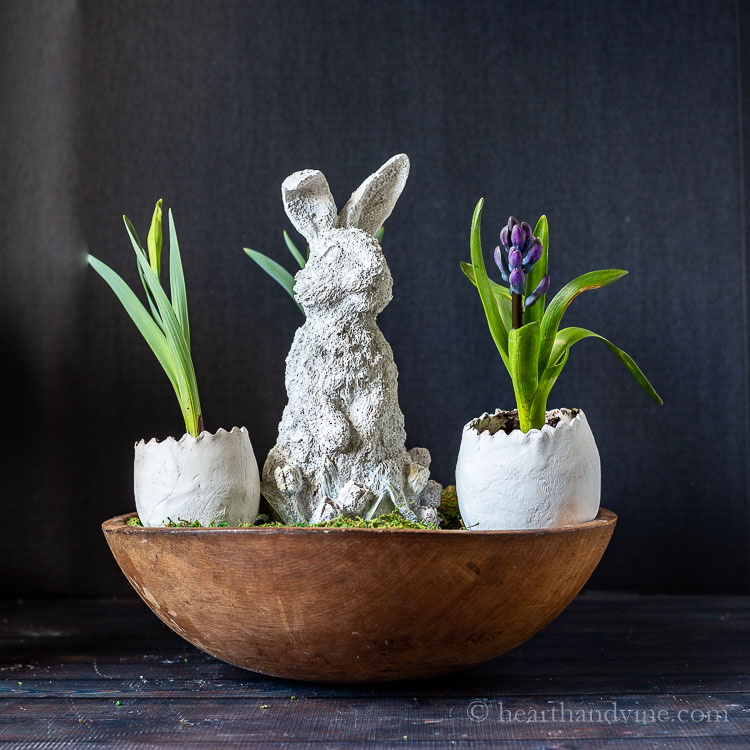 Cement bunny and clay eggs with flowers in vintage dough bowl