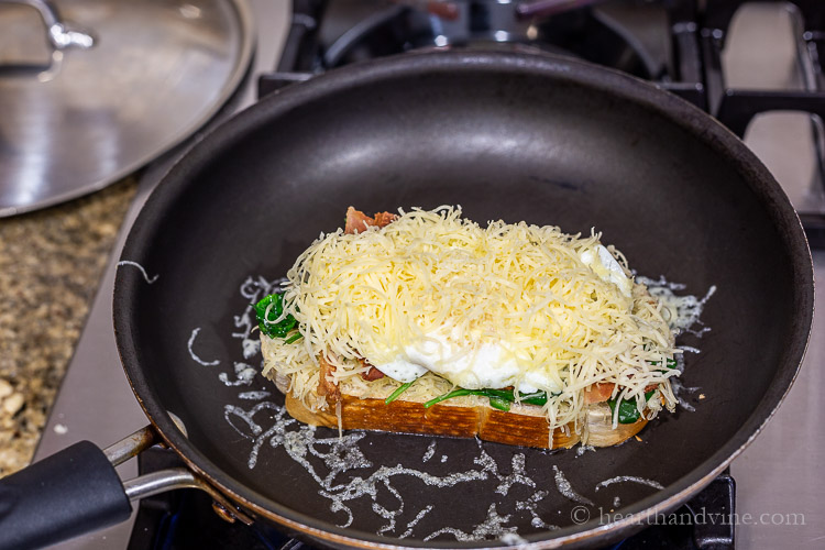Breakfast grilled cheese layers with gouda cheese, spinach, bacon and fried egg