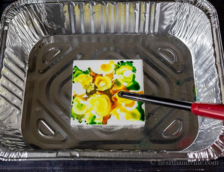 Using a torch to set the alcohol ink on fire.