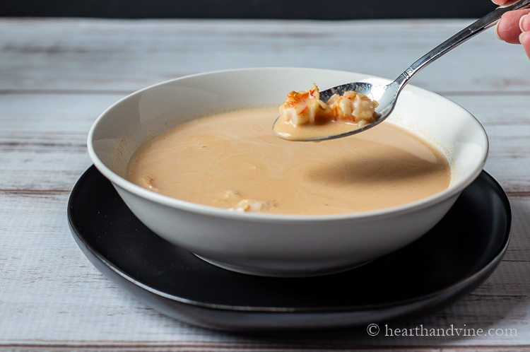 Spoon of shrimp and some bisque over bowl of shrimp bisque soup.