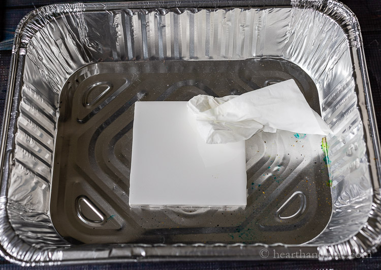 Cleaning a ceramic tile with rubbing alcohol.