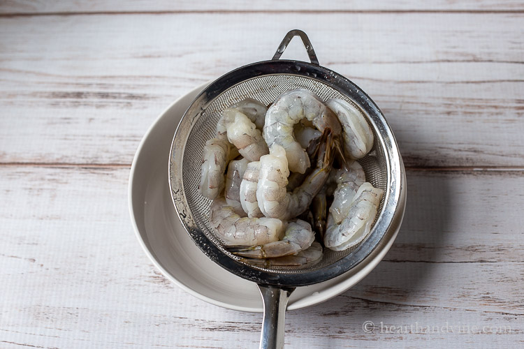 raw shrimp in strainer