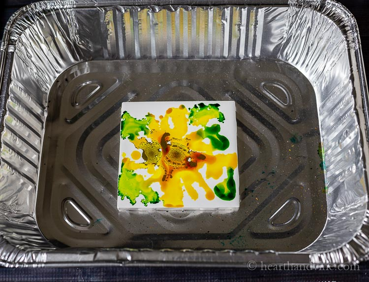 Adding more alcohol inks to a ceramic tile.