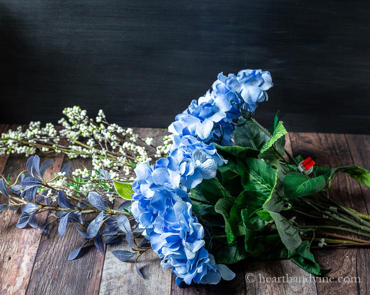 Artificial blue hydrangea flowers and other long stemmed branches.