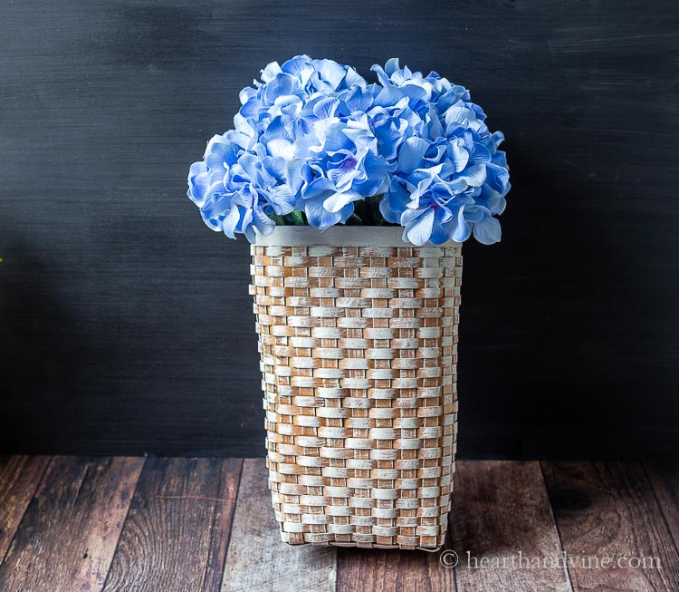 Blue artificial hydrangea flowers in whitewashed wooden basket.