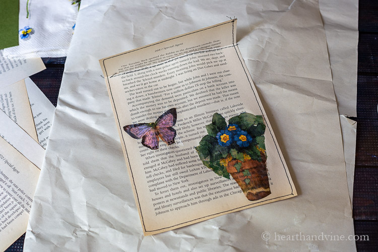 Adding napkin butterfly and pot of pansies with mod podge to book page.