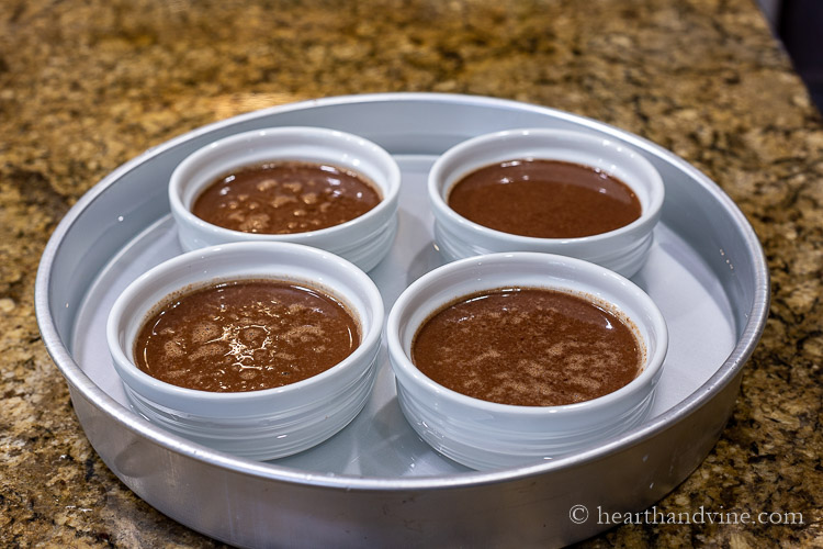 4 ramekins in water bath with chocolate mixture.