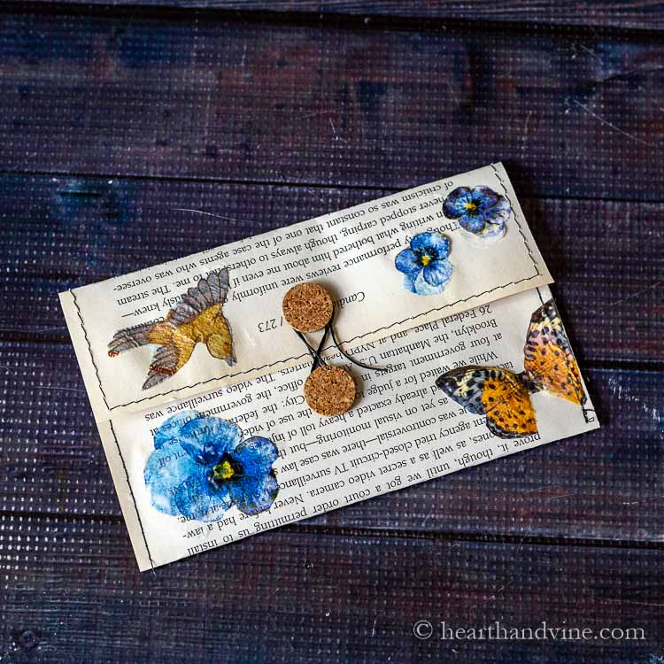 Decoupaged flowers, butterfy and bird from napkins to book page.