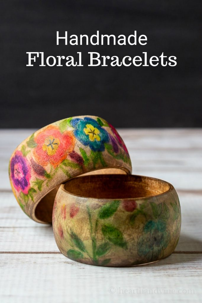 Two wood bracelets with flowers and leaves colored in and darkened with stain.