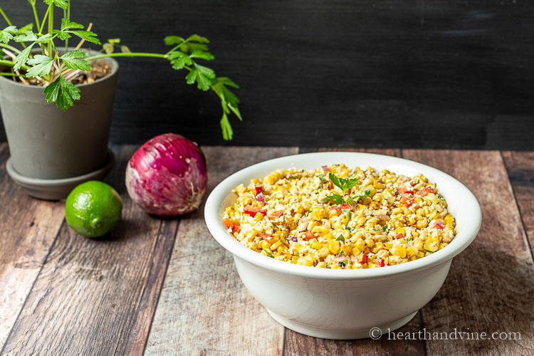 Bowl of Mexican street corn with red onion, a lime and pot of parsley next to it.