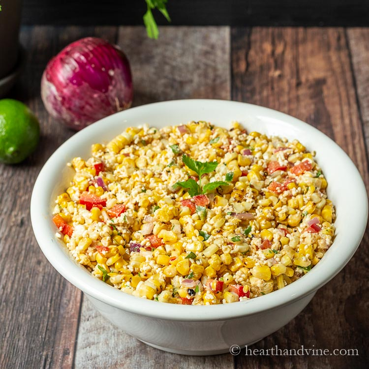 Mexican street corn salad in a white bowl with a red onion and lime next to it on the table.