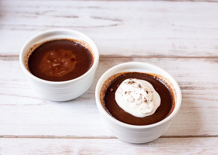 Two ramekins with chocolate pot de creme. One has whipped cream and chocolate savings.
