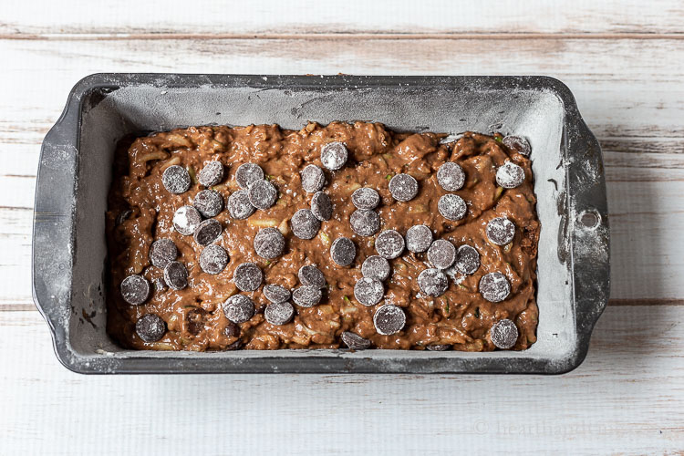 Chocolate zucchini bread batter with chocolate chips on top.