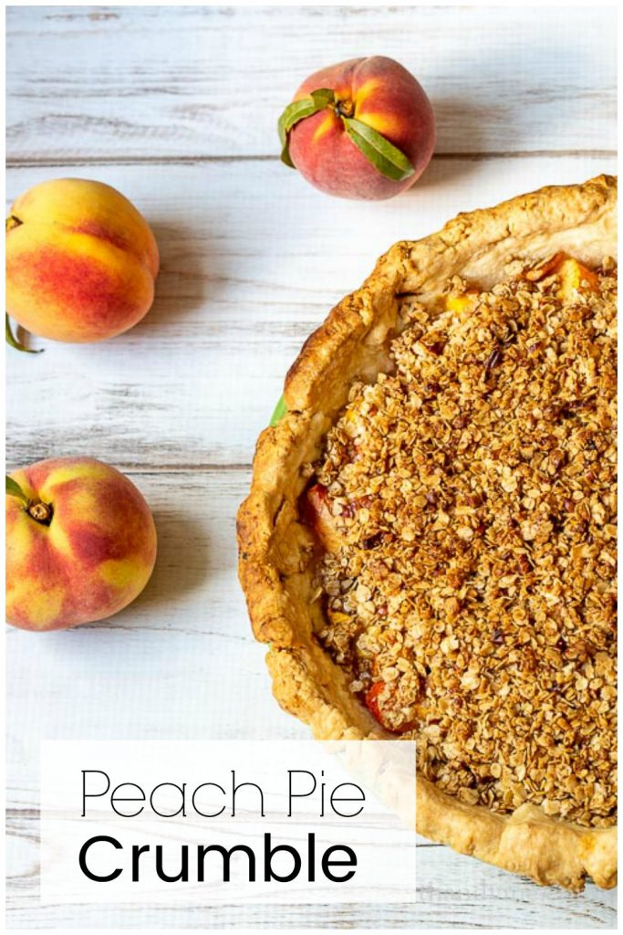 Partial aerial view of peach pie with crisp topping and a couple of fresh peaches on the side.