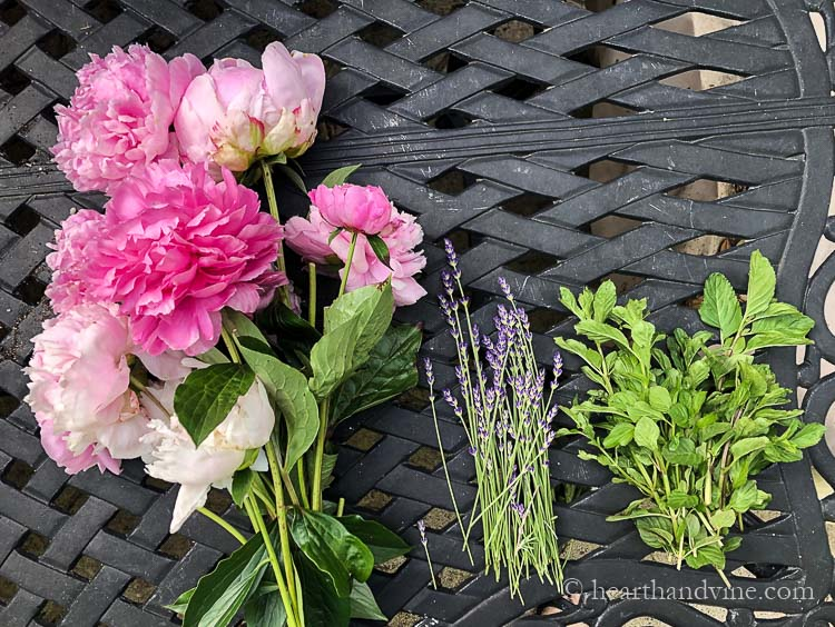 Fresh peonies, lavender and mint on a table.