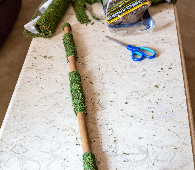 Sheet moss attached on the wooden broom stick in areas, and scissors on table.