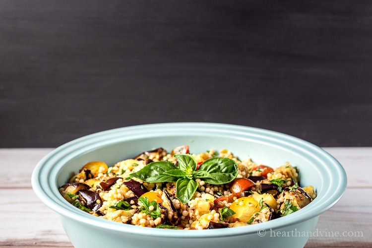 Close view of grilled eggplant salad in a large blue serving bowl.