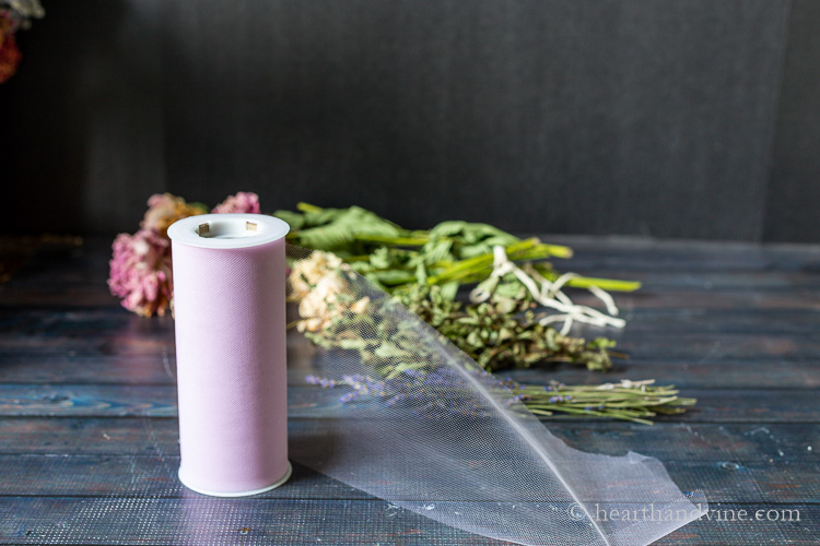 Lilac colored spool of tulle in front of dried flowers.