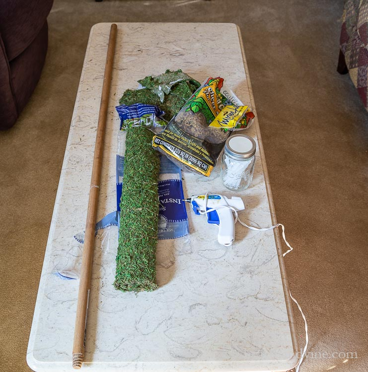 Old broom stick, sheet moss, glue gun, glue sticks on a table.