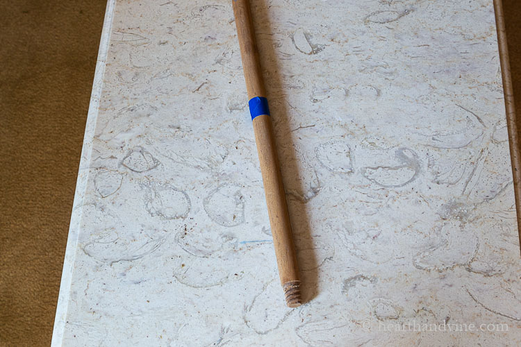Old broom stick with blue tape near the end.