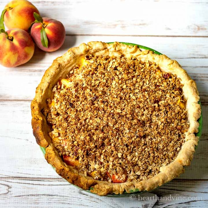 Peach pie crumble aerial view with 3 peaches on the side.