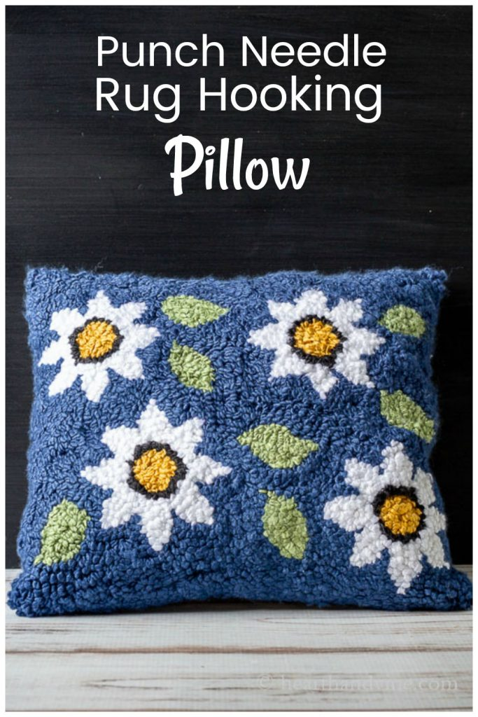 Punch needle rug hooking pillow in a floral pattern with a blue background.