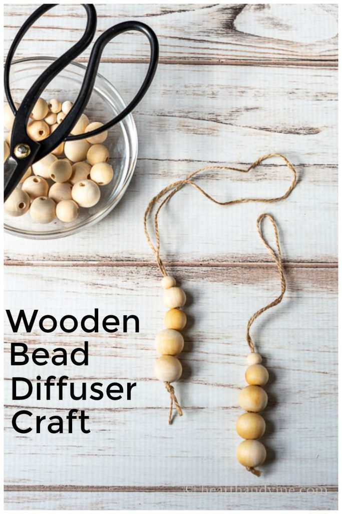 Two wooden bead diffusers on twine next to a bowl of wood beads and a pair of scissors.