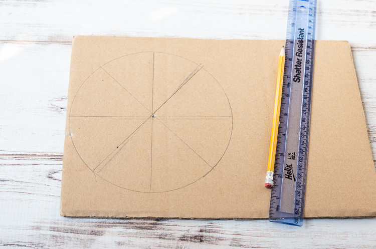Ruler, pencil and cardboard with a circle and 4 dividing lines through the center.