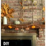 Partial view of fall mantel with multi-colored twine pumpkin garland, oak leaves and branch window frame.
