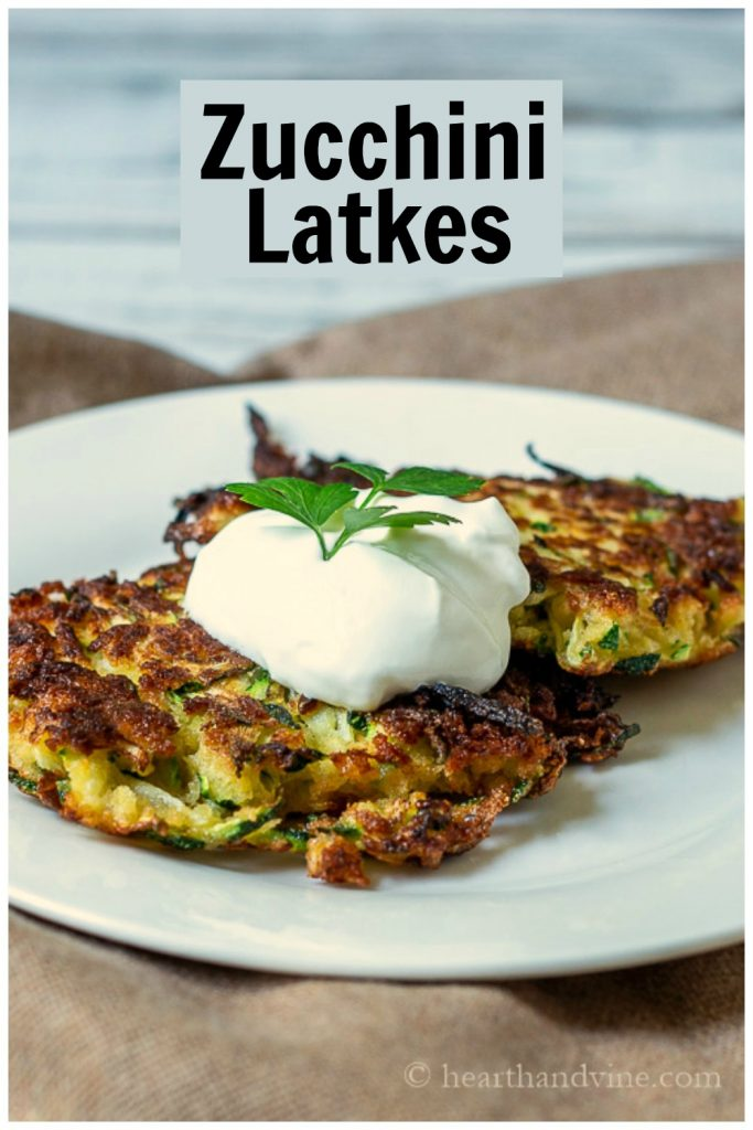 Two zucchini latkes on a plate with sour cream.