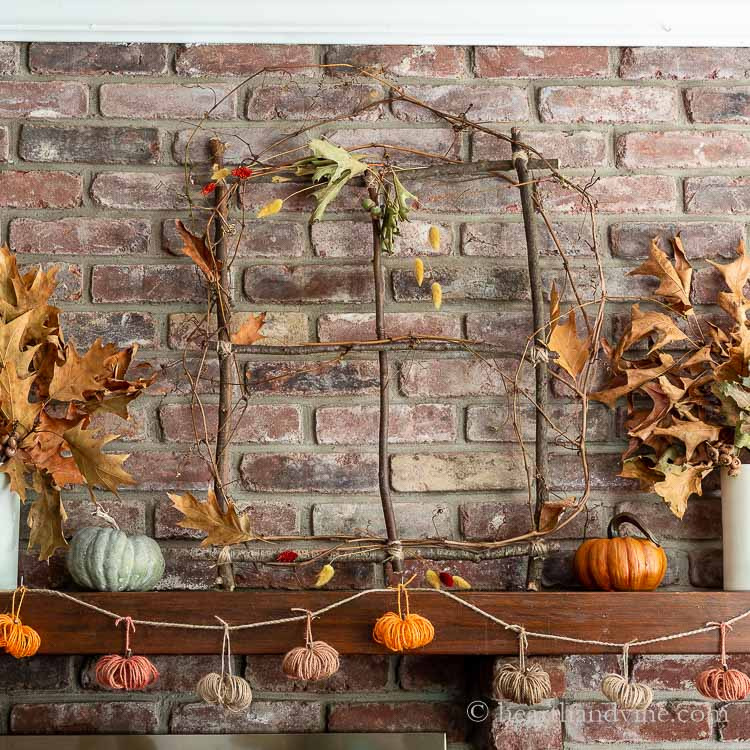 Decorated branch window on mantel with fall leaves and twine pumpkin garland.