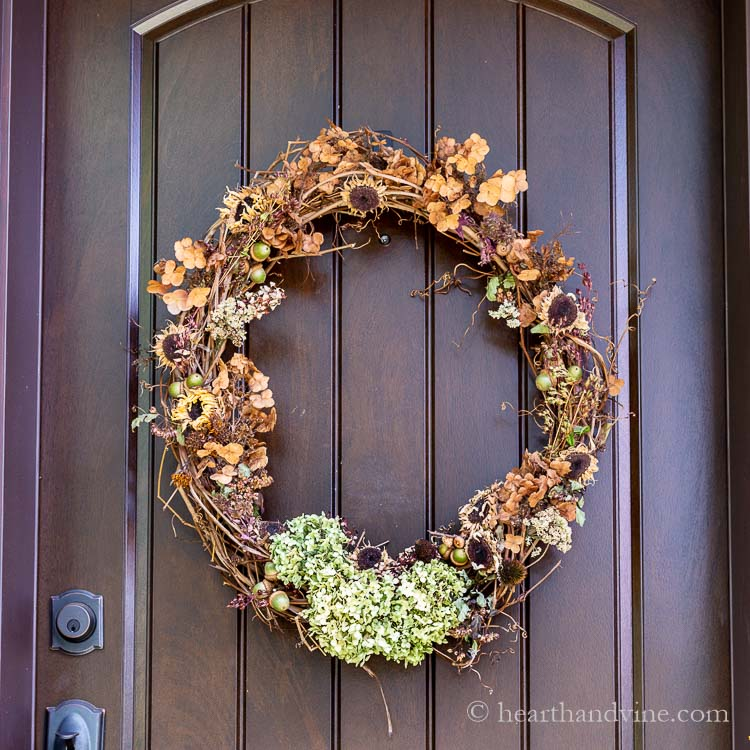A natural fall wreath hanging on the front door from backyard plants, trees and other natural elements.