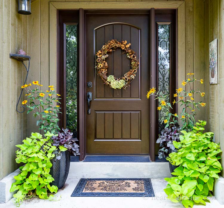 Fall front porch with flower planters and a natural fall wreath on the door.