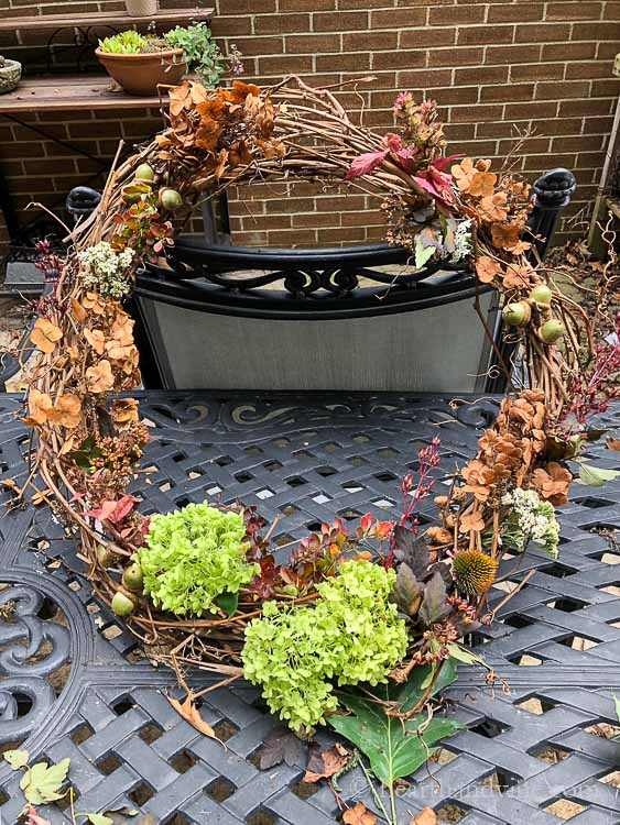Partially finished grape vine wreath with dried plant materials decorating the wreath.