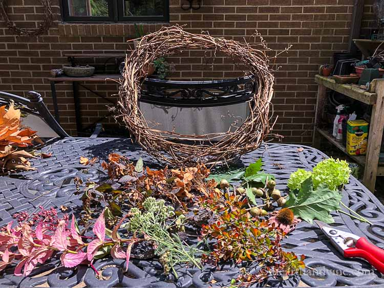 Grapevine wreath and cuttings from trees, perennials and shrubs on table.
