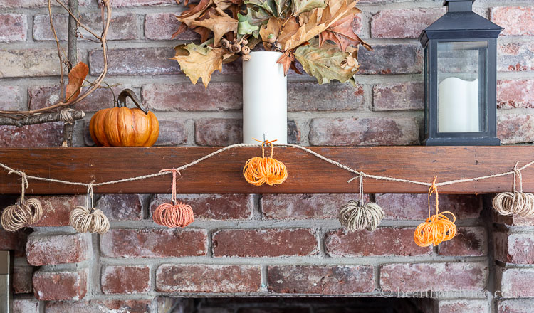 Fall mantel with twine pumpkin garland.