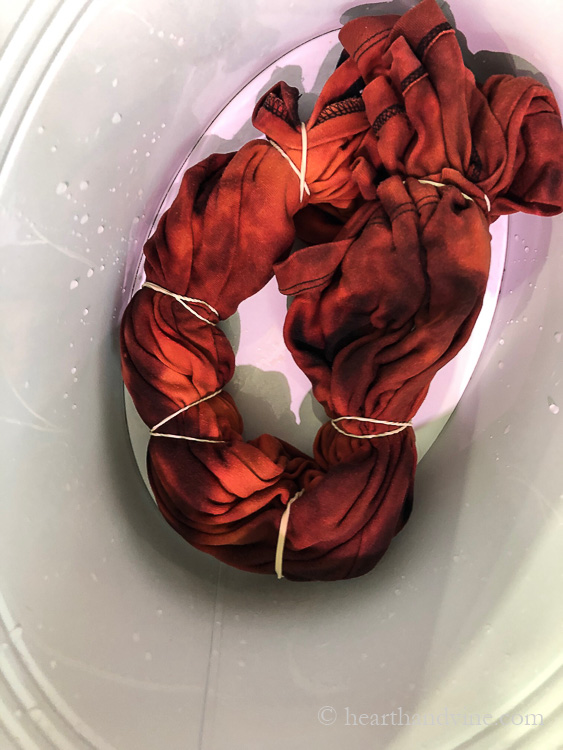 Long sleeve black shirt wrapped in rubber bands after bleach solution has been poured over it.