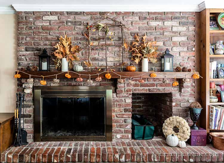 Full image of the entire wall with fireplace with the mantel decorated for fall using branches, leaves and a twine pumpkin garland.