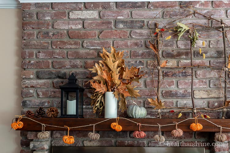 Left side of fall mantel showing pine cones, a black lantern, a white vase with oak leaves a faux green pumpkin and a branch window. Hanging from the mantel is a twine pumpkin garland.
