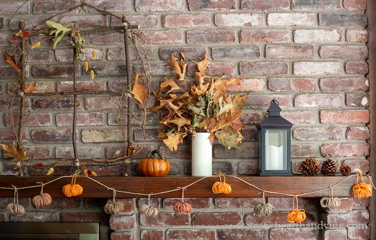 Right side of a rustic fall mantel showing pine cones, a black lantern, a white vase with oak leaves a faux green pumpkin and a branch window. Hanging from the mantel is a multi-colored twine pumpkin garland.