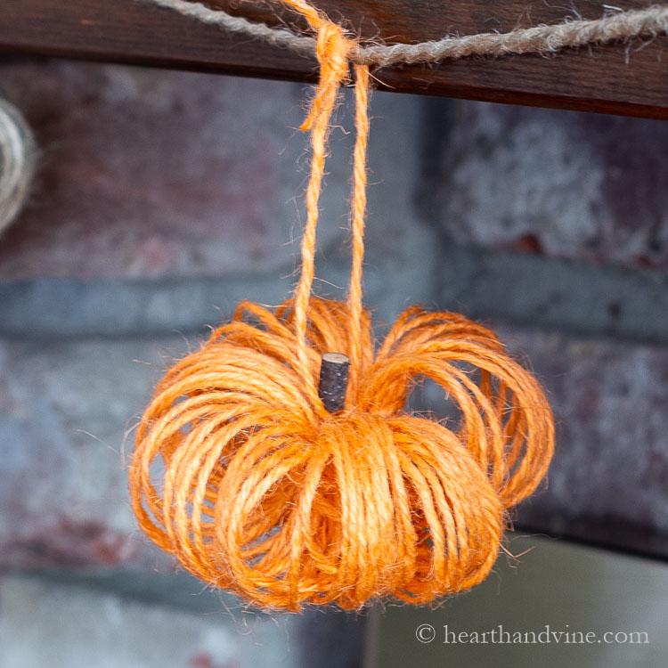 Orange twine pumpkin hanging from a garland.