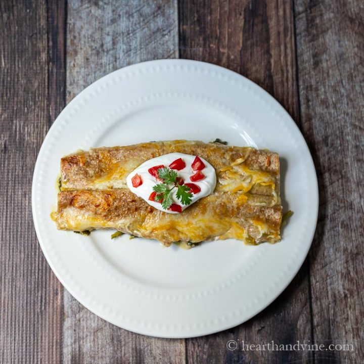 Two spinach enchiladas with sour cream, tomatoes and cilantro on top.