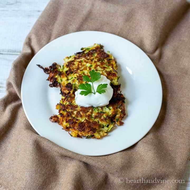 Two zucchini latkas on a plate topped with sour cream and parsley
