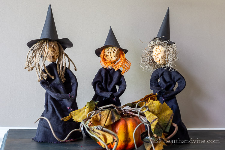 Three dried apple dolls dressed as witches on a table around a pumpkin.