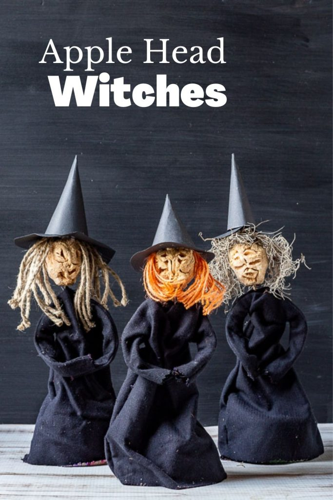 Three witches made from dried carved apples for heads, paper hats and black fabric dresses.
