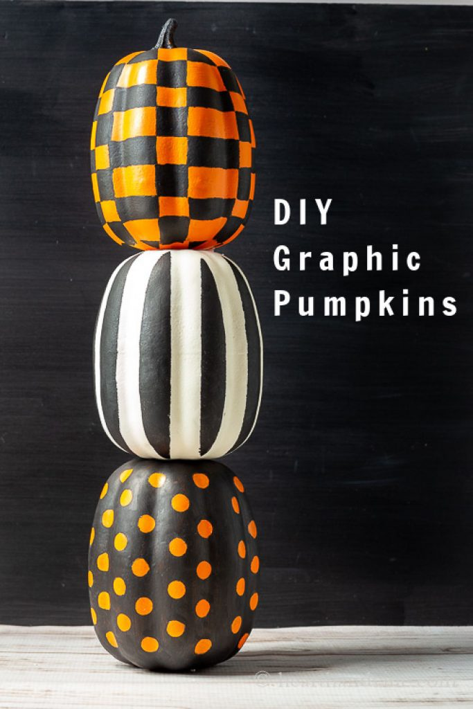 Painted stacked pumpkins in a modern graphic print. One is polka dots, one is striped and the last is plaid.